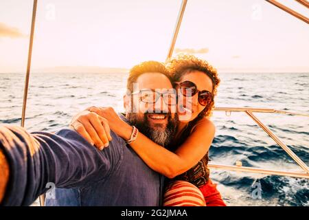Cheerful and happy young adult couple smile and enjoy the sail boat yacht trip in summer day holiday vacation travel adventure lifestyle - love and romantic life
