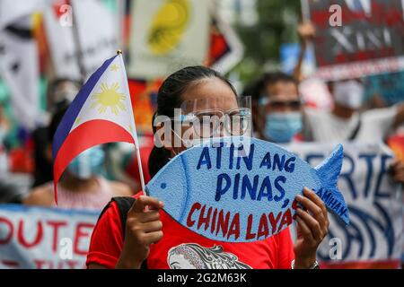 Metro Manila, Philippines. 12th June 2021. An activist holds a placard in front of the Chinese consulate during a protest to mark Independence Day in the financial district of Makati. Various groups called on China to stop its maritime activities in the disputed South China Sea, which endangers peace and stability in the region. Credit: Majority World CIC/Alamy Live News