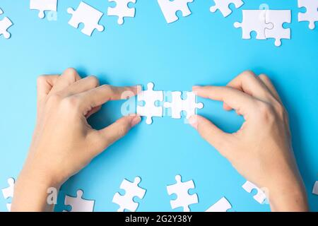 hands connecting couple white puzzle jigsaw pieces on blue background. Concept of solutions, mission, success, goals, cooperation, partnership, strate