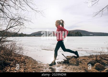Spring running girl training outside jogging by the lake in nature countryside. Woman athlete runner exercising cardio
