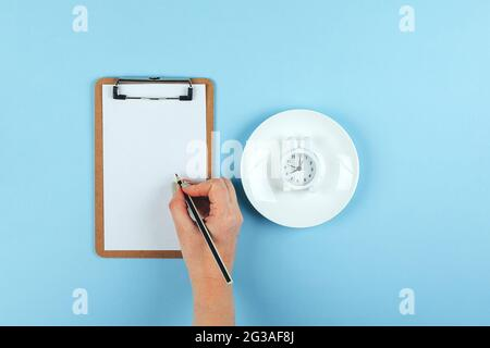 Intermittent fasting, ketogenic, diet concept. Plate with white alarm clock