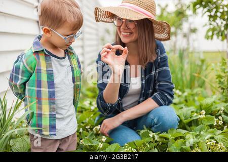 Child and mother gardening in strawberry plant garden in backyard