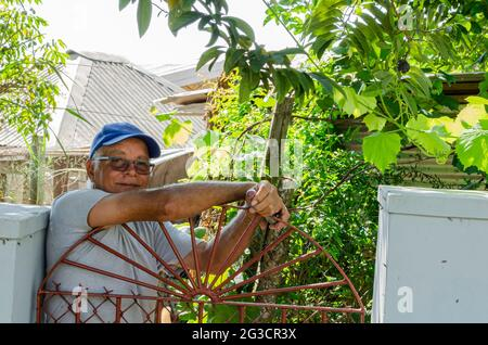 Jamaican Senior Man Looking Out From Behind His Gate