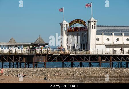 Entrance to Palace Pier on the Brighton, East Sussex UK sea front, showing illuminated neon sign.