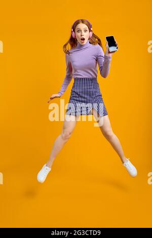 Full length body size view of nice cheerful cheery woman in headhones jumping having fun using smartphone fast speed connection, listen to music, isol