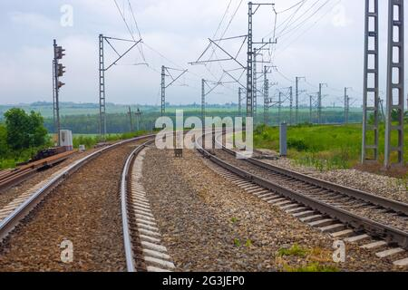 Railway tracks with a turn on the background of nature in summer. Road for travel and tourism.