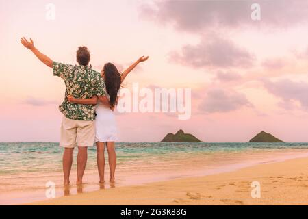 Happy beach vacation couple tourists enjoying sunset with arms up in freedom view from behind. Woman and man standing in hawaiian shirt against ocean