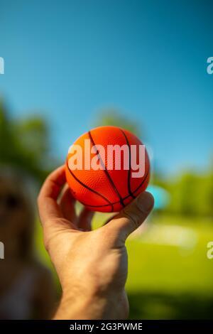 Bright orange mini basketball in a hand