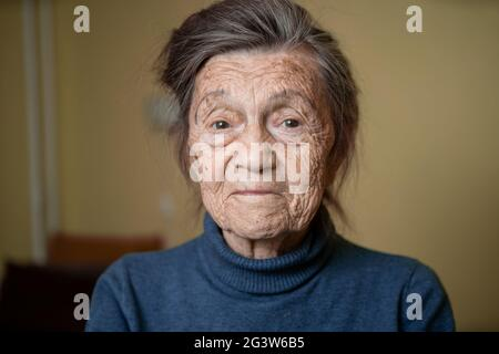90 year old cute elderly woman with gray hair and wrinkles face, wearing sweater, portrait large, smiling and looking joyfully,