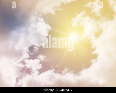 sun shining in piercing in clouds with lens flare, toned