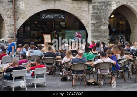 Uzes, Provence, France 06.19.21 Men and women sitting outside a cafe watching a live football match on large screen. Medieval stone arches. drinting.