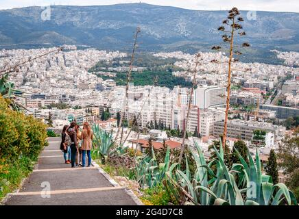 Athens, Greece - April 4 2015: Young girls enjoy the view from the trail that leads to Lycabettus mount. Athens and Hymettus mount are in the backgrou