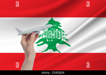 Airplane in hand with national flag of Lebanon. Travel to Lebanon.