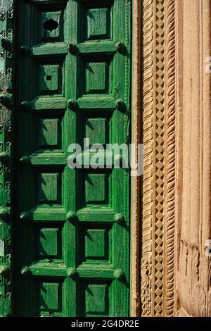 Old wooden green door with designer wall at varanasi (India) street