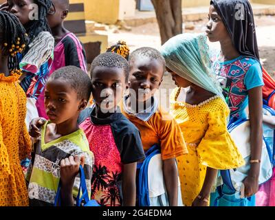 MBOUR, SENEGAL - DECEMBER Circa, 2020. Group of unidentified teenagers standing up in playground of the school , outdoors on a sunny summer day. Waiti
