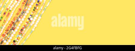 Banner with necklaces made from beads and pearls on a yellow background with place for text.
