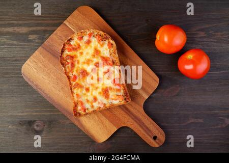 Top view of fresh baked homemade pizza toast with pair of fresh tomatoes