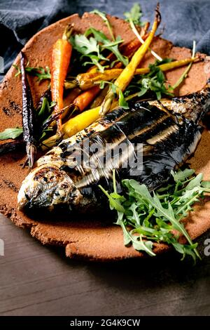 Grilled cooked fresh gutted sea bream or dorado fish on ceramic plate wrapped in bamboo leaves served with herbs, colorful carrots, blue napkin over d
