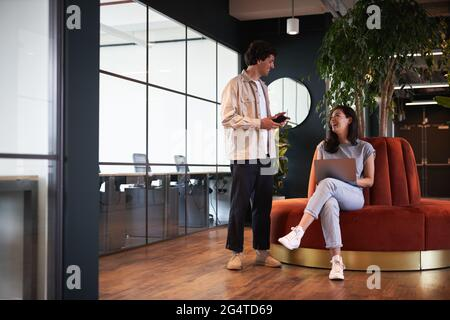 Casually dressed young man and woman working in modern open plan office having informal meeting sitting on orange circular sofa