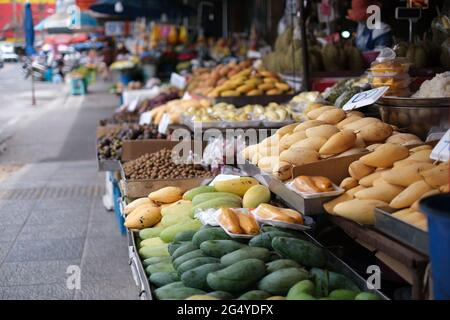 Stalls at a typical street market in Thailand, full of fresh fruits and vegetables