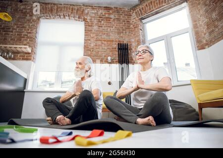 Healthy retired couple in sport clothes sitting on yoga mat and meditating with hands joined near chest. Active man and woman practising lotus pose at home.