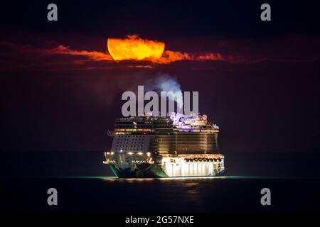 Weymouth, Dorset, UK.  25th June 2021.  UK Weather.  The almost full Strawberry supermoon glows orange as it shines through a small break in the clouds above the empty NCL cruise ship Norwegian Escape which is anchored in the bay at Weymouth in Dorset.  Picture Credit: Graham Hunt/Alamy Live News
