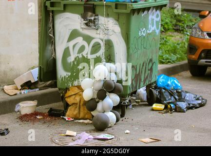 Green metal dirty can, dumpster full of trash, garbage. Trash bags, black white balloons are lying on a floor after a party celebration near the bins.