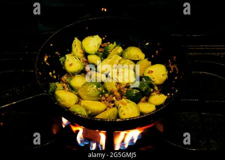 brussels sprouts and beef bacon cooking in a saute pan on fire