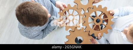 Business people holding wooden gears in office top view