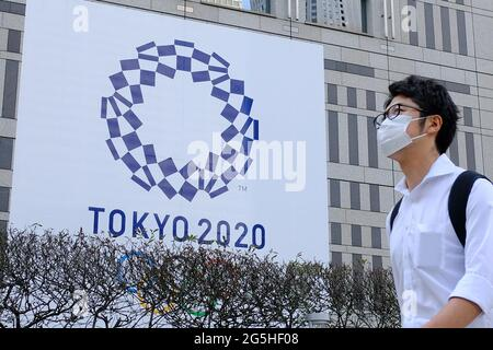 Tokyo, Japan. 25th June, 2021. A man wearing a face mask as a preventive measure against the spread of coronavirus walks past a banner for the upcoming Tokyo 2020 Olympics in front of the Tokyo Metro Government building. Credit: SOPA Images Limited/Alamy Live News