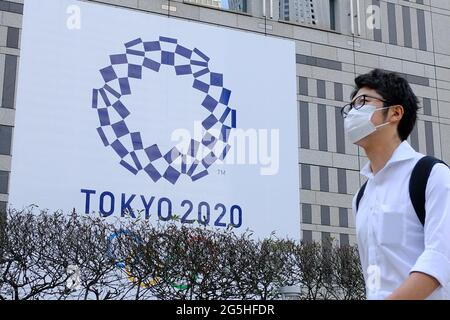 Tokyo, Japan. 25th June, 2021. A man wearing a face mask as a preventive measure against the spread of coronavirus walks past a banner for the upcoming Tokyo 2020 Olympics in front of the Tokyo Metro Government building. Credit: James Matsumoto/SOPA Images/ZUMA Wire/Alamy Live News