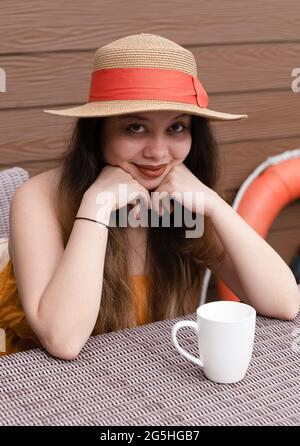 Girl with beautiful long hair wearing a straw hat sitting in front of a coffee mug sitting on a terrace in a summer luxury resort