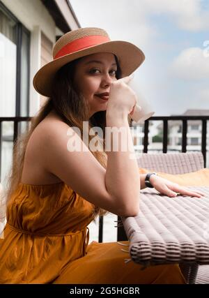 Girl with beautiful long hair wearing a straw hat holds a coffee in her hands while sitting on a terrace in a summer luxury resort