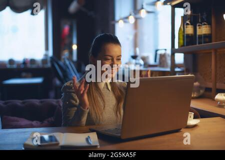Young beautiful woman sits at a wooden table in a cafe indoors and works on a laptop. Conception of remote work and freelance work.