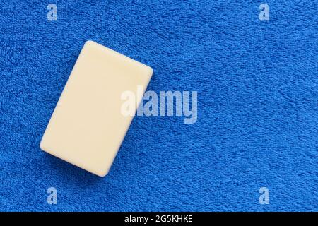 White bar of soap on fluffy rustic towel blue with copy space, hygiene concept