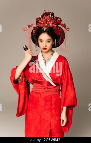 Asian woman holding sword and looking at camera isolated on grey
