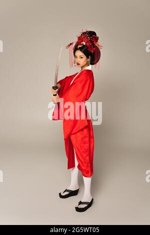 Full length of asian woman holding sword on grey background