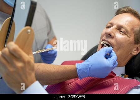 Fragment photo of middle-aged man doing teeth-whitening in clinic