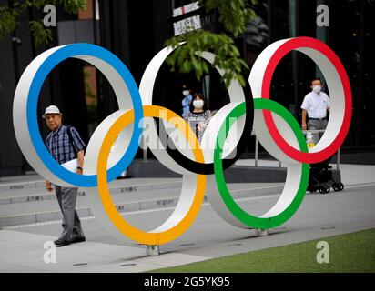 Kohei Jinno, 87, who was forced to leave his house two times ahead of the 1964 and 2020 Olympics Games to make way for construction of the main stadium, walks next to the Olympic Rings monument outside the Japan Olympic Museum near the National Stadium, the main stadium for the 2020 Tokyo Olympic Games that have been postponed to 2021 due to the coronavirus disease (COVID-19) pandemic, in Tokyo, Japan June 24, 2021. Picture taken June 24, 2021.    REUTERS/Issei Kato