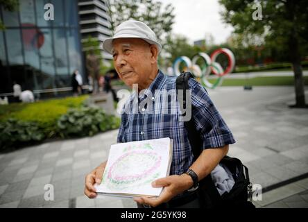 Kohei Jinno, 87, who was forced to leave his house two times ahead of the 1964 and 2020 Olympics Games to make way for construction of the main stadium, speaks in front of the Olympic Rings monument outside the Japan Olympic Museum near the National Stadium, the main stadium for the 2020 Tokyo Olympic Games that have been postponed to 2021 due to the coronavirus disease (COVID-19) pandemic, in Tokyo, Japan June 24, 2021. Picture taken June 24, 2021.  REUTERS/Issei Kato