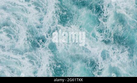 3D rendering of a top view of turquoise waves with foam. Water splash in the sea, ocean on a bright sunny day