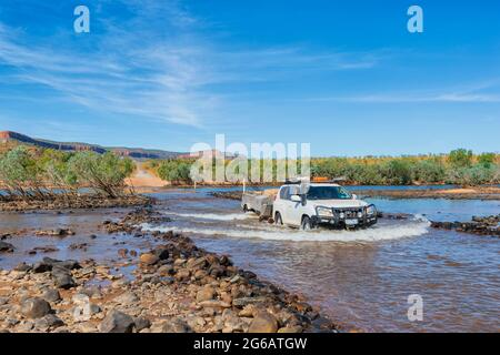 Off-road car towing a trailer crossing the iconic Pentecost Crossing, Gibb River Road, the Kimberley, Western Australia, WA, Australia