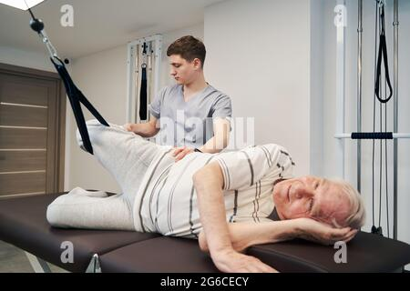 Elderly patient doing suspension training exercise with right leg
