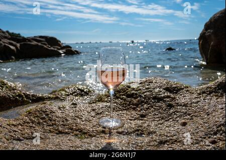 Summer time in Provence, glass of cold rose wine on sandy beach near Saint-Tropez in sunny day, Var department, France