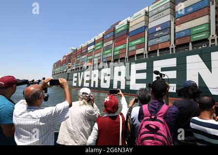 Ismailia, Egypt. 7th July, 2021. People take photos of the Ever Given container ship sailing on the Suez Canal in Ismailia Province, Egypt, July 7, 2021. The Ever Given container ship which blocked the Suez Canal for nearly a week in March began its journey out of the canal on Wednesday, said Suez Canal Authority (SCA) Chairman Osama Rabie. The SCA has held the giant ship in a lake between two stretches of the waterway since it was re-floated on March 29, as the dispute over requested compensation by the SCA was not settled. Credit: Ahmed Gomaa/Xinhua/Alamy Live News