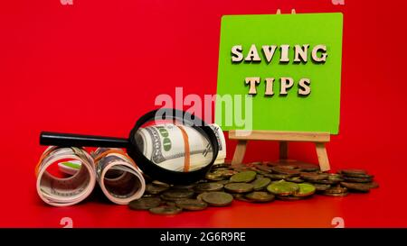 Money saving tips concept. Selective focus on the green board  with a text saving tips. How to save money fro holiday, paying loan or investment conce