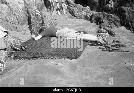 1950s, historical, a young woman with rolled-up trousers, lying face down on a rug besides some rocks on a flat, small sandy area of a beach having a rest, England, UK. Probably exhausted after building sandcastles for her children.