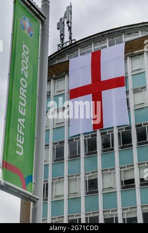 Wembley Park, UK. 10th July 2021.   Football's Coming Home,  Wembley Park is buzzing with excitement ahead of Sundays match and local businesses get behind the England team.     A giant England flag, the St Georges Cross, covers two floors of the College of North West London.   60,000 fans are set to descend to Wembley Park to watch England play Italy in the UEFA EURO 2020 Finals at Wembley Stadium on Sunday 11th July.  Amanda Rose/Alamy Live News