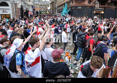 London, UK. 11th July, 2021. England football fans celebrating in Leicester Square ahead of the Italy v England Euros 2000 final in Leicester Square, London, and creating a huge amount of rubbish. Credit: Paul Brown/Alamy Live News
