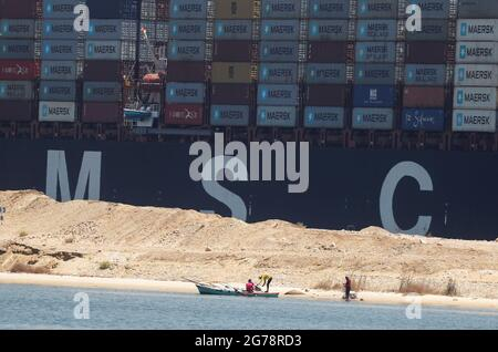 An MSC container ship passes through the Suez Canal near fishermen and their boat, in Ismailia, Egypt July 7, 2021. Picture taken July 7, 2021. REUTERS/Amr Abdallah Dalsh